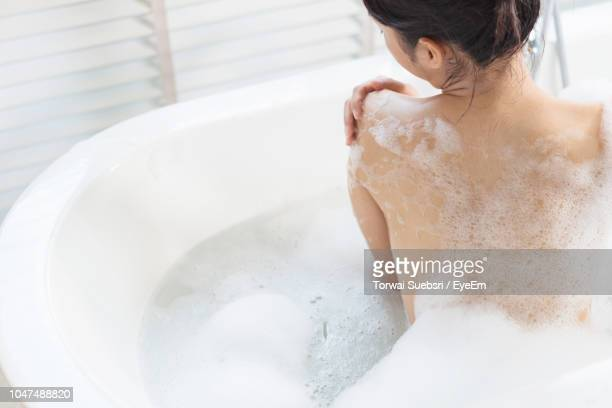 rear view of topless young woman taking bath in bathtub - torwai stock pictures, royalty-free photos & images