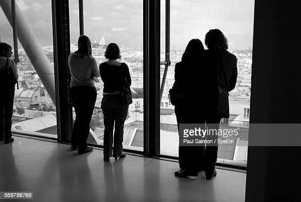 Rear View Of Tourist Looking At Cityscape With Montmartre In Background From Glass Window