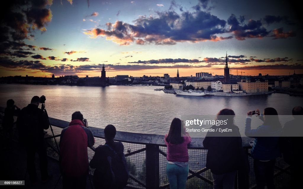 Rear View Of Tourist Standing By Lake While Photographing Cityscape At Sunset : Stock Photo