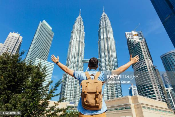 rear view of tourist with backpack spreading arms to kuala lumpur skyline with petronas towers - malaysia stock pictures, royalty-free photos & images