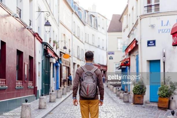 rear view of tourist with backpack walking through the narrow streets of montmartre district, paris, france - village photos et images de collection