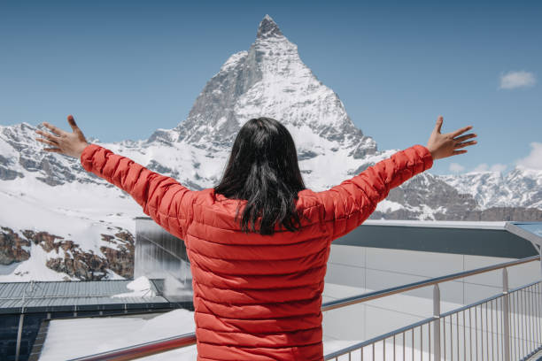 Rear View of Tourist Woman Enjoying Freedom Happy While Taking Breath Of Fresh Air Against Snowcapped Mountain Backgrounds.