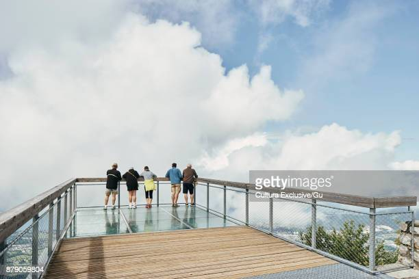Rear view of tourists looking down from viewing platform at Mont Revard, Auvergne-Rhone-Alpes, France