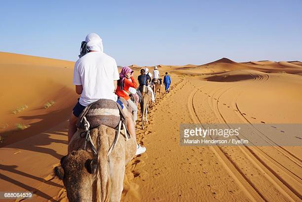 Rear View Of Tourists Riding On Camels In Sahara Desert