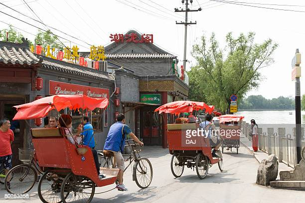 rear view of tourists sitting in chinese rickshaw, china, beijing, hutong   - rickshaw stock photos and pictures
