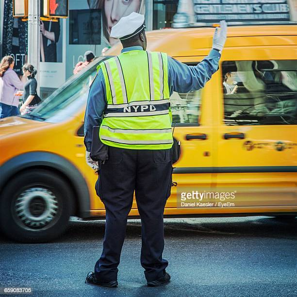 Rear View Of Traffic Cop Controlling Traffic On Street