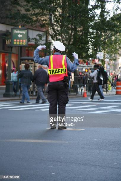 Rear View Of Traffic Cop Standing On Street In City