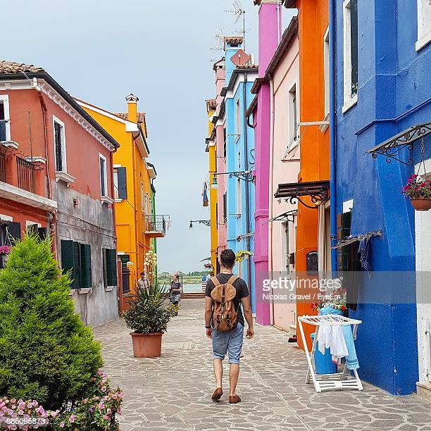 Rear View Of Traveler Walking On Alley Amidst Multi Colored Buildings At Burano