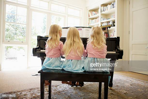 Rear View of Triplets Playing Piano in Living Room