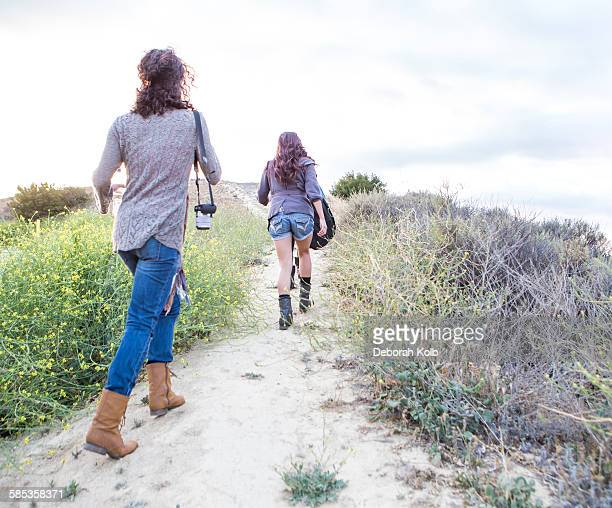 Rear view of two adult sisters walking along dirt track