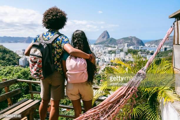 vista traseira de dois mochileiros olhando a vista do pão de açúcar - rio de janeiro - fotografias e filmes do acervo