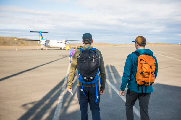 Rear view of two backpackers walking on tarmac towards an airplane