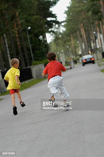 Rear view of two boys playing on the road