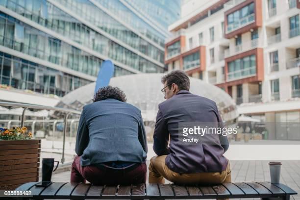 Rückansicht der beiden Unternehmer sittin auf der Bank