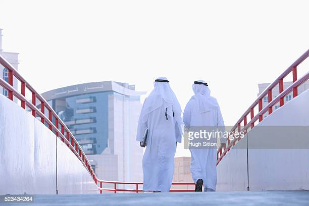 rear view of two businessmen wearing traditional clothing walking on walkway - hugh sitton stock pictures, royalty-free photos & images