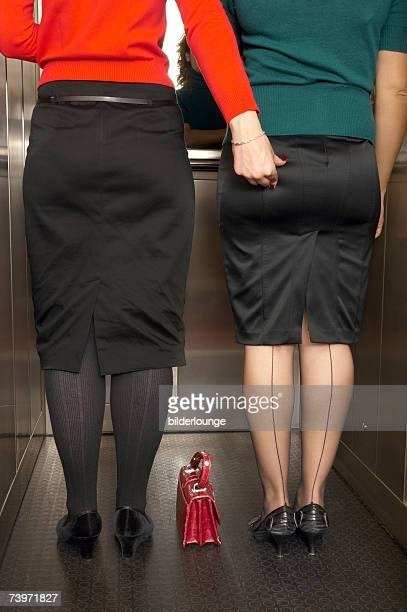 rear view of two businesswomen standing in elevator one pinching her colleague in the bottom