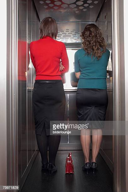 rear view of two businesswomen standing in elevator together - seamed stockings stock photos and pictures