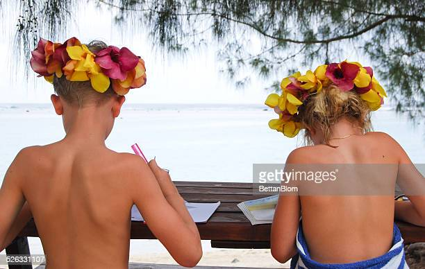 Rear view of two Children studying on beach, Cook Islands