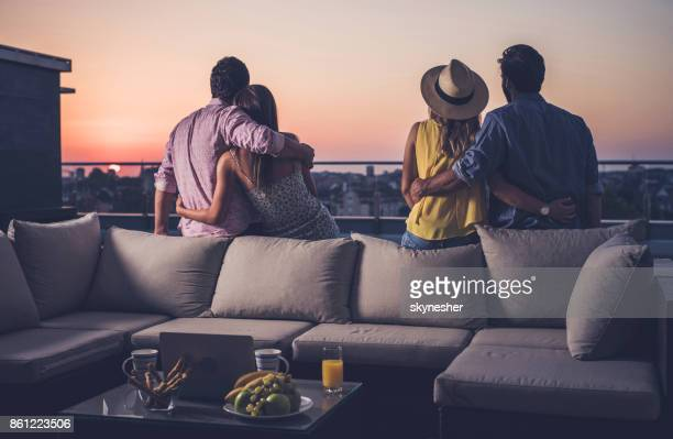 rear view of two embraced couples looking at sunrise from a penthouse terrace. - women of penthouse stock photos and pictures