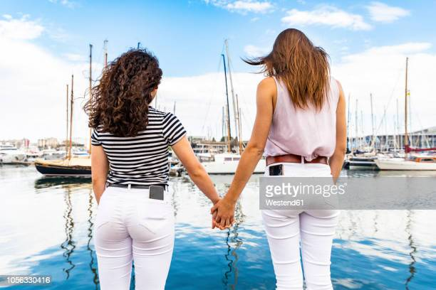 rear view of two female friends holding hands at a marina - white trousers stock pictures, royalty-free photos & images