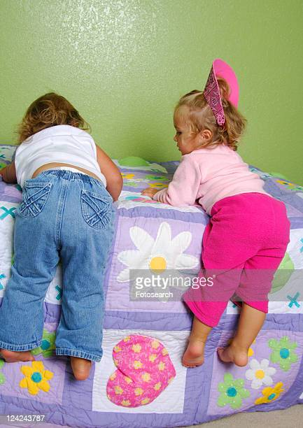 rear view of two girls climbing on the bed - little girls bare bum stock pictures, royalty-free photos & images