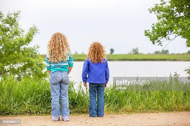 Vue arrière de deux filles regardant le lac