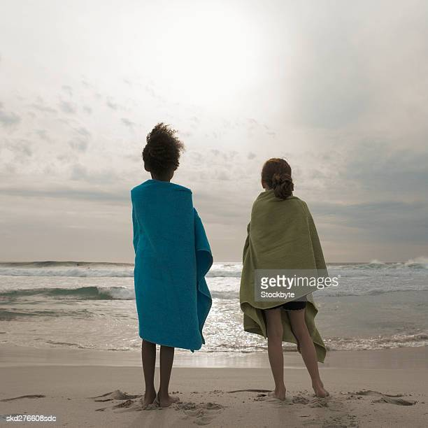 Rear view of two girls standing on beach with towel wrapped around them (10-11)