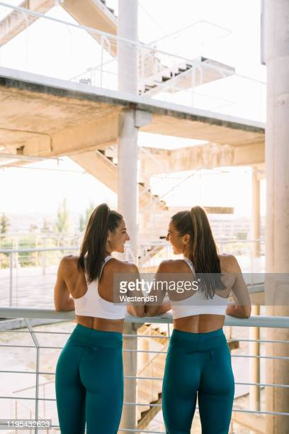 rear view of two happy twin sisters relaxing after doing sports - bunda imagens e fotografias de stock