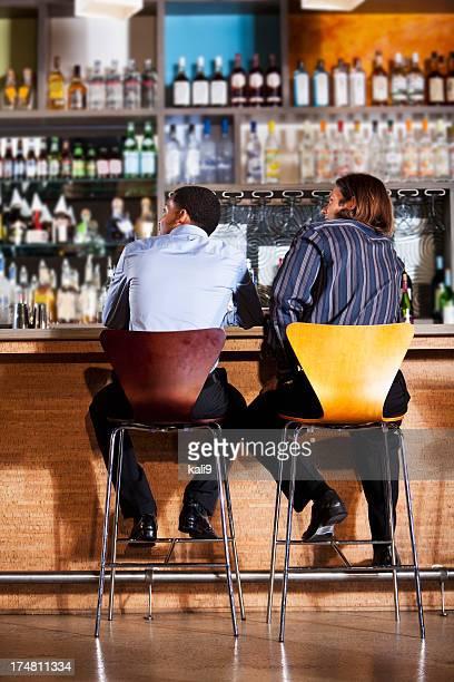 Rear view of two men at bar