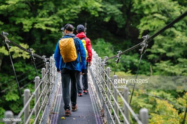 雨の中でハイキングしながら吊り橋を渡る 2 人の後姿 - つり橋 ストックフォトと画像