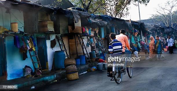 Rear view of two men cycling on the street, Mumbai, Maharashtra, India