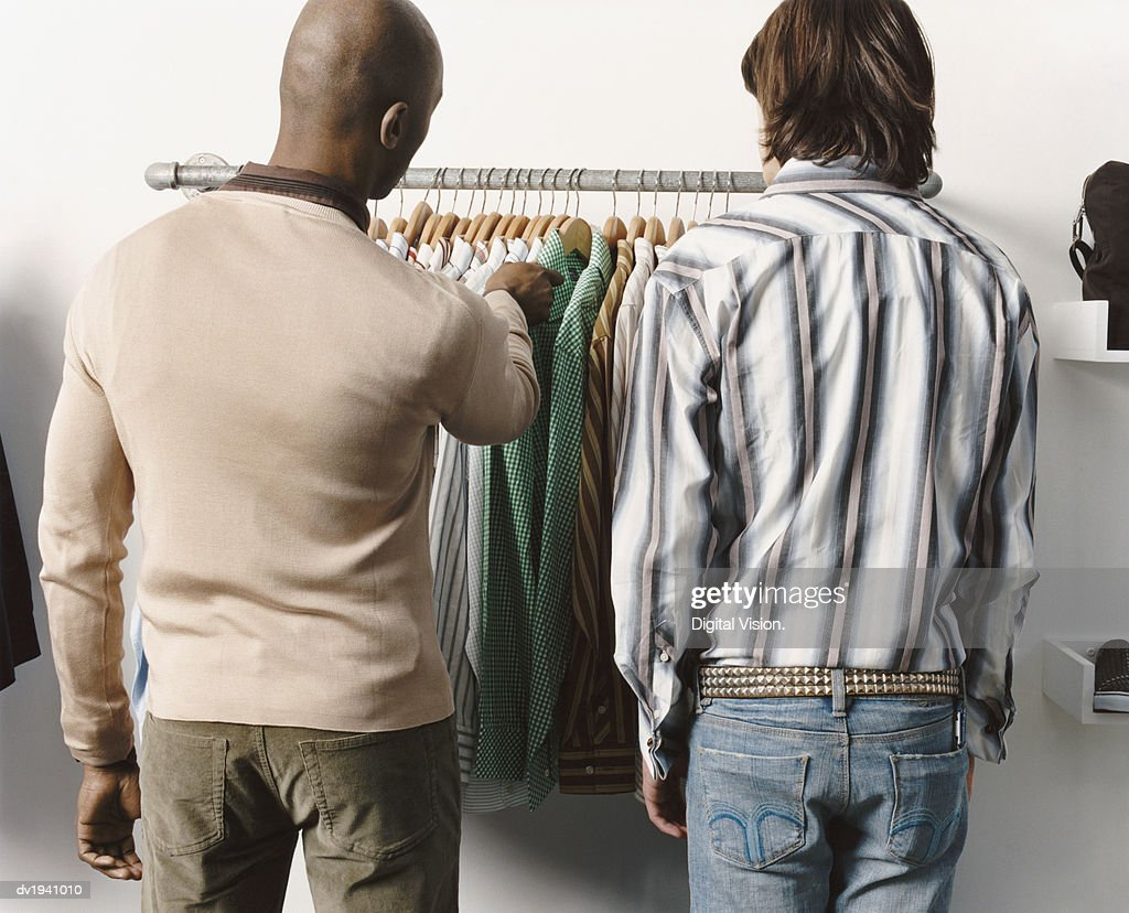 Rear View of Two Men Looking at Shirts on a Clothes Rail : Stock Photo