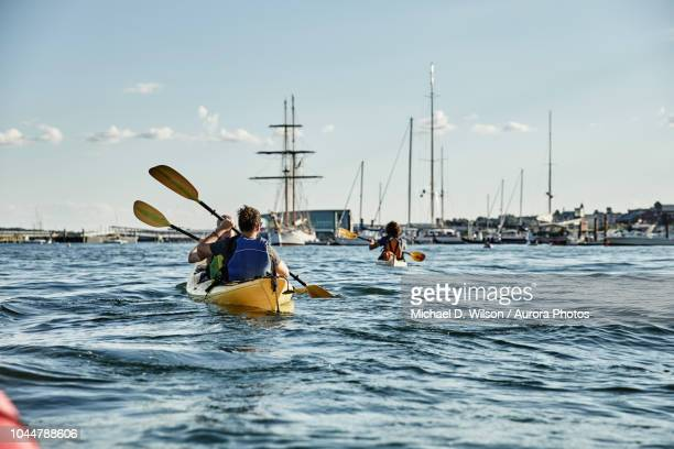 rear view of two men paddling in tandem sea kayak, casco bay, portland, maine, usa - portland maine fotografías e imágenes de stock