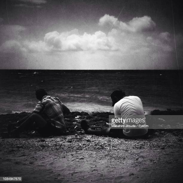 rear view of two men relaxing at beach - men stockfoto's en -beelden