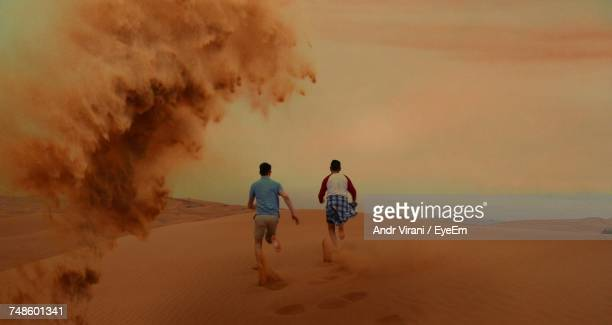 rear view of two men running on sand dune - runaway stock photos and pictures