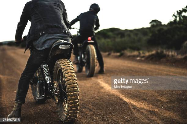 Rear view of two men sitting on cafe racer motorcycles on a dusty dirt road.