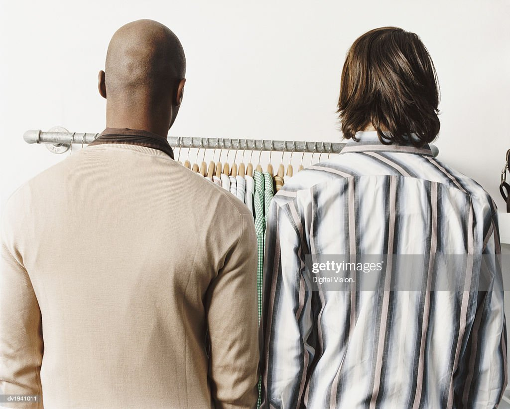 Rear View of Two Men Standing Side By Side, Looking at Shirts on a Clothes Rail : Stock Photo