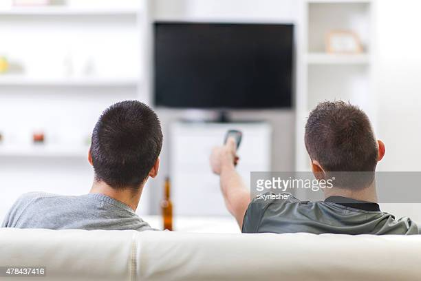 Rear view of two men watching TV at home.