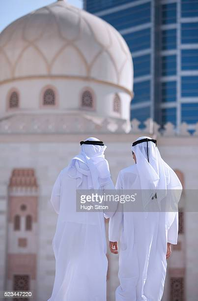 rear view of two men wearing traditional clothing walking on street, mosque and office building in background, dubai, u.a.e - hugh sitton stock-fotos und bilder