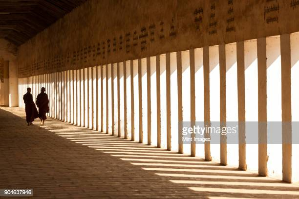 Rear view of two monks walking along sunlit colonnade of pagoda.