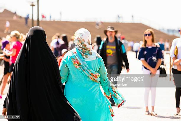 Rear view of two muslim woman in crowd of people