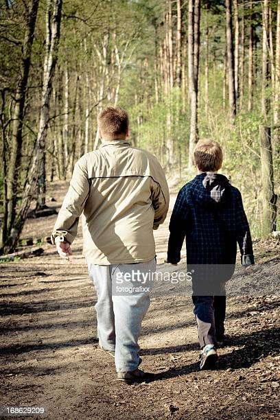 rear view of two overweight boys walk through the forest - chubby boy stock photos and pictures