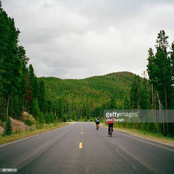 Rear view of two people cycling on a road, Rocky Mountain National Park, Colorado, USA