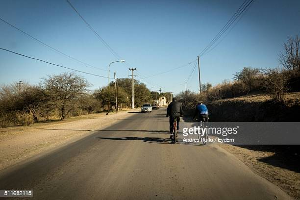 rear view of two people cycling on country road - andres ruffo stock photos and pictures
