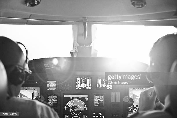 Rear view of two pilots sitting in cockpit of airplane