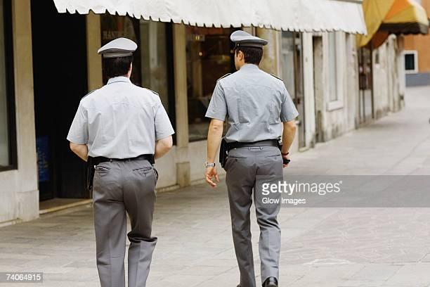 Rear view of two policemen walking towards a building, Venice, Veneto, Italy