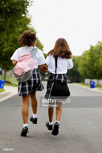 Rear view of two schoolgirls walking with holding hands