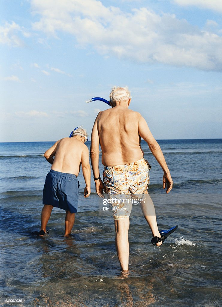 Rear View of Two Senior Men Wading Into the Sea With Flippers : Stock Photo