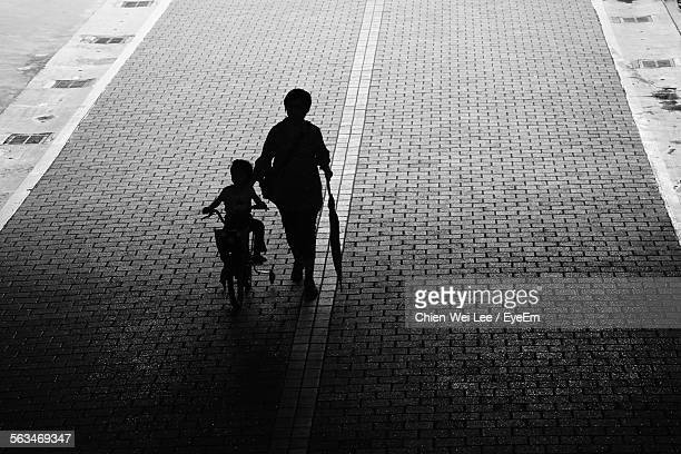 Rear View Of Two Silhouette Children On Cobblestone Street