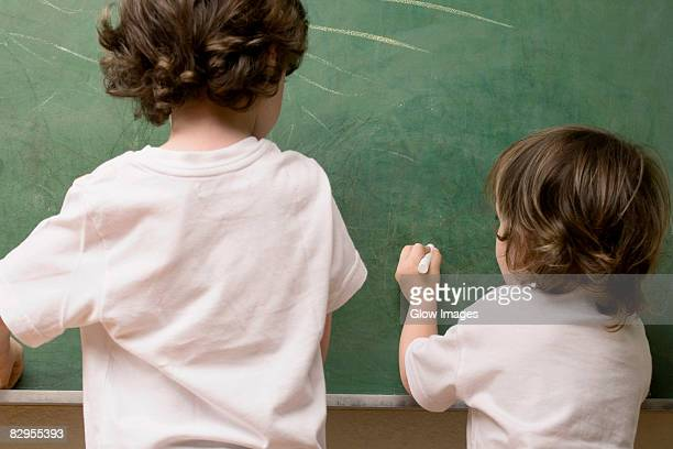 Rear view of two students drawing on a blackboard